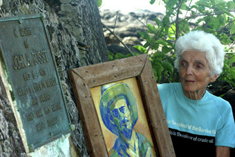 Margaret Thorsborne holds a self-portarait of reef campaigner John Busst at his Bingil Bay memorial plaque